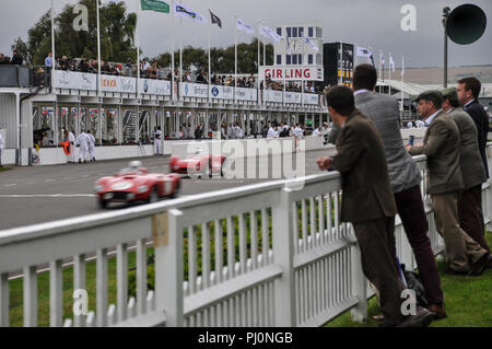The Goodwood Revival The Freddie March Memorial Trophy race, endurance evening race, with people in period costume watching. Racing cars - Stock Photo