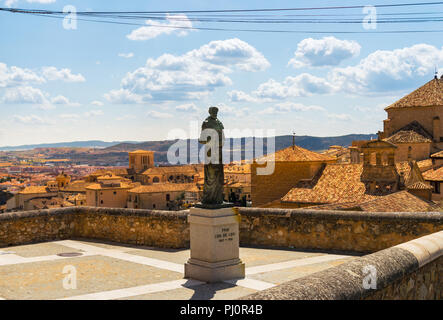 Statue of the poet and religious Fray Luis de Leon in the upper part of the old town of Cuenca, Spain. Houses and mountains on the background. - Stock Photo