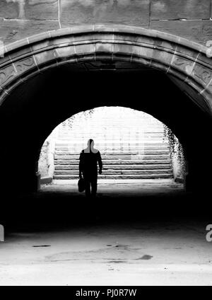 Businessman walking through underpass in Central Park, New York - Stock Photo