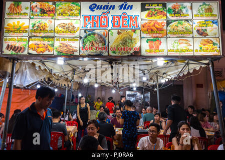 Ho Chi Minh City, Vietnam - April 28, 2018: open air night street restaurant at Ben Thanh Market. Signboard shows the menu with pictures, dishes names - Stock Photo