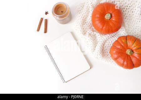 Autumn cozy composition. Mockup scene with blank notebook. Pumpkins, candle, cinnamon sticks and knitted plaid on white table background. Thanksgiving, fall, halloween concept. Flat lay, top view. - Stock Photo
