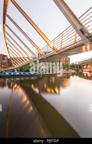 Early evening underneath Merchant's Bridge on the Bridgewater Canal in Castelfield, Manchester, showing a moored narrowboat - Stock Photo