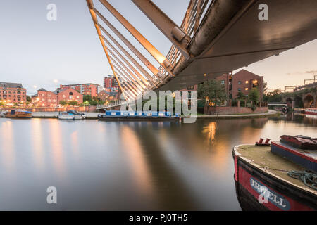 Early evening underneath Merchant's Bridge on the Bridgewater Canal in Castelfield, Manchester, showing part of a moored narrowboat - Stock Photo