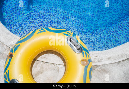 Yellow inflatable rubber ring / tube on the edge of a pool in summer - Stock Photo