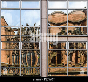 Warped reflections of John Ryland's Library in the windows of an opposite building on Deansgate in Manchester - Stock Photo
