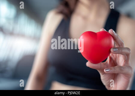 Close up of red massage ball like heart shape in fitness woman hand at sport gym training center. Medical and healthcare of heart attack and serious i - Stock Photo