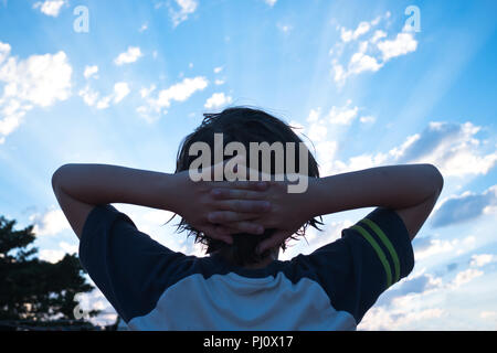 rear view of 11 year old boy with his arms outstretched and his head resting in his hands, looking up at the sky during sunset in Menorca, Spain - Stock Photo