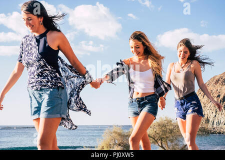 three young caucasian  pretty girls walking together taking hands eachother smiling and laughing. cheerful concept of happy women in outdoor leisure a - Stock Photo