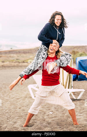 couple of caucasian young people man and female enjoy the summer beach. the man carry the female on his shoulder and both laugh like crazy while stay  - Stock Photo