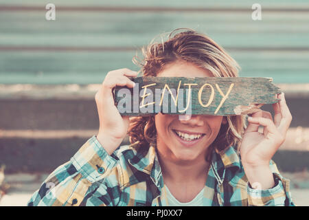 smiled young caucasian boy cover his beautiful face with a piece of wood written with enjoy message. urban background. vintage finlter picture for pos - Stock Photo