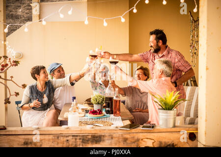 group of adults mixed ages from 40 to 80 celebrate together at home in the terrace with food and wine. friendship together people concept having fun a - Stock Photo