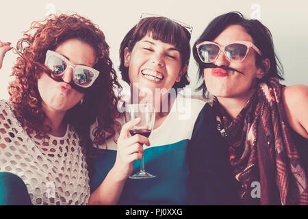 three caucasian females friends stay together in friendship and craziness using hair like moustache and happiness relationship concept. vintage full c - Stock Photo