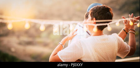 happy caucasian people dancing together at home in terrace with lights during the sunset. romantic and relationship concept image for happy people in  - Stock Photo
