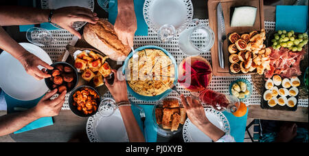 Food Catering Cuisine Culinary Gourmet Buffet Party Concept with lot of hands taking food from various mixed place on the table. having fu. community  - Stock Photo