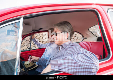 nice adult couple hug and love inside a red old vintage car parked on the road. smiles and have fun traveling together. happiness and lifestyle for ni - Stock Photo