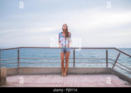 Full length portrait of beautiful young woman standing with the ocean and water blue in background and sky listening music with headphones. modern con - Stock Photo