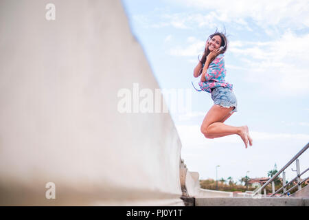 Happiness concept with young beautiful girl jumping with joyful against a white sky blue background. sea side place. Cheerful caucasian woman smile an - Stock Photo