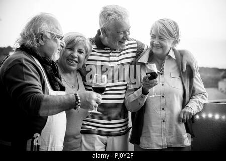 celebration event outdoor for a group of adult people. drkinking wine in the rooftop terrace with nice view on the background. happy lifestyle togethe - Stock Photo