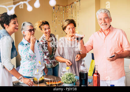 happy group of cheerful caucasian man and women mixed ages having fun together eating and rinking to celebrate. smile and laugh people enjoying the fr - Stock Photo
