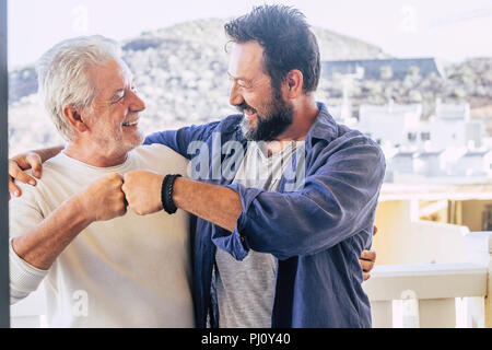 Two happy male friends father and son having a good time together giving friendly punch eachother. city and mountains in background. caucasian people  - Stock Photo