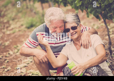 senior adult couple laugh in happines together forever playing with soap bubbles in the country yard outdoor leisure activity. stay young concept and  - Stock Photo