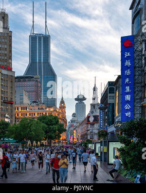 A crowd walks through People's Square in Shanghai China, as the sun sets on a beautiful summer day. - Stock Photo