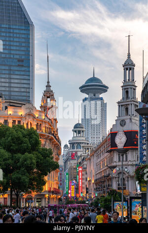 A crowd walks along a street near People's Square in Shanghai China, as the sun sets on a beautiful summer day. - Stock Photo