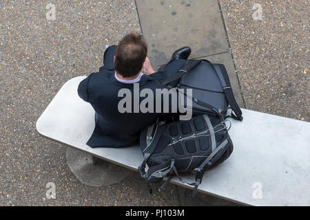a businessman sitting on a metal seat in the city of London checking his smartphone or mobile device wearing a suit with luggage and bags by his side. - Stock Photo