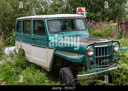 AUGUST 12 2018 - McCarthy Alaska: An old rusted out Jeep truck sits in a field with a vintage Pizza Hut delivery sign on top - Stock Photo