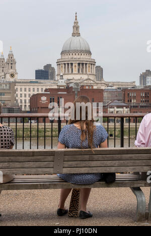 young woman sitting on a bench eating her lunch on a break from the office  looking across the river thames towards st paul's cathedral. - Stock Photo