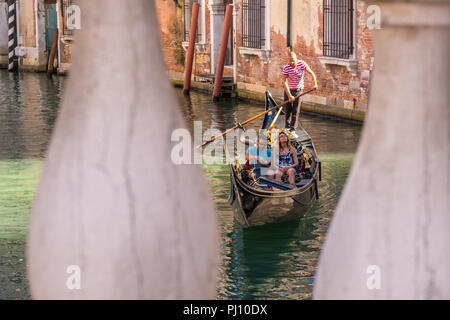 Venice, Italy - 15.08.2018: Traditional Gondolas on narrow canal between colorful historic houses in Venice. - Stock Photo