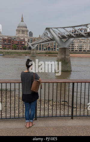 young woman looking across the river thames in central London at st paul's cathedral and the millennium bridge. - Stock Photo