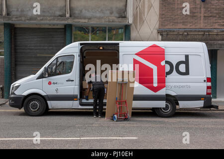 a dpd distribution parcel and package delivery driver delivering a large parcel to a business address in central london.