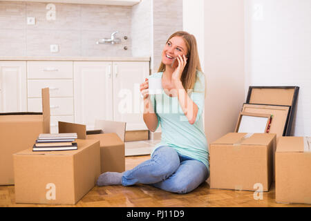 Beautiful woman drinking coffee and talking on the phone while moving into her new apartment. - Stock Photo