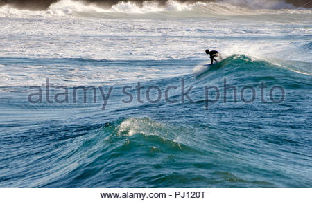 A lone surfer silhouetted - crouching on his surfboard - catching a nice wave during a period of big swell; at Turners Beach, Yamba, NSW, Australia. - Stock Photo