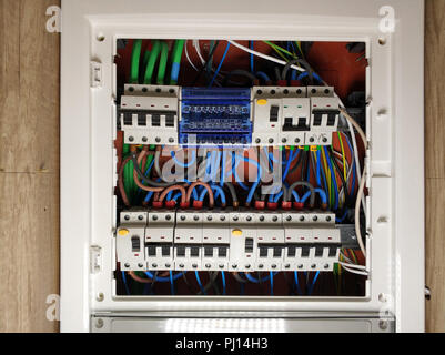Close up of white frame panel electrical switch board, with colourful cables automatic circuit switchers breakers and fuses - Stock Photo