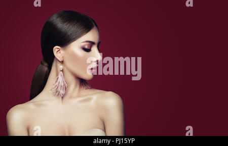 Young perfect woman with makeup, healthy hair, fashion jewelry earrings on red background. Earrings with pearls and feathers - Stock Photo