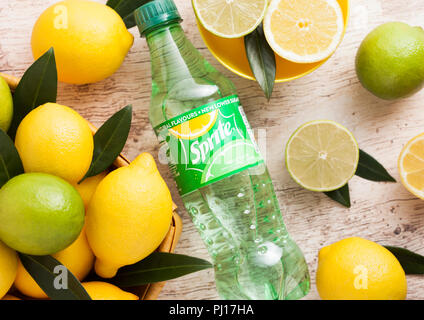 LONDON, UK - SEPTEMBER 03, 2018: Bottle of Sprite drink on wooden background with lemons and limes. Sprite is lemon-like flavored soft drink produced  - Stock Photo