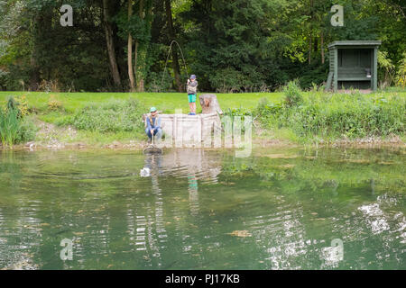 Nine year old boy trout fishing at Church Paddock Trout Fishery, Winchester, United Kingdom. - Stock Photo