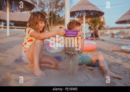 Happy positive children sitting on a towel on the beach and playing with sand. Kids having fun on a sandy beach - Stock Photo
