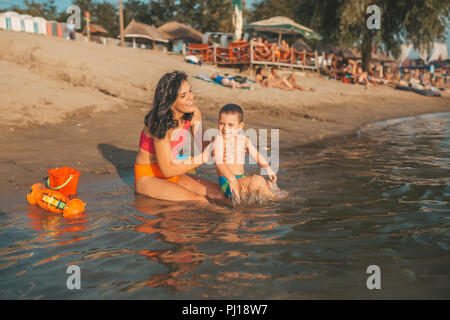 Three year old toddler boy playing with beach toys with mother on beach. Happy family. Vacation, travel concept - Stock Photo