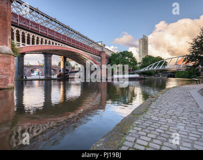 Early morning view from the tow path alongside Bridgewater Canal in Castlefield, Manchester, showing the MSJAR and Merchant's bridges and the Hilton - Stock Photo
