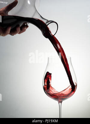Red wine being poured in a glass. - Stock Photo
