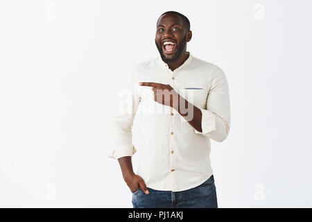 Ha-ha look at that weirdo. Portrait of happy emotive good-looking dark-skinned man with beard, laughing out loud joyfully, having fun on party, wearing trendy clothes and pointing left with forefinger - Stock Photo