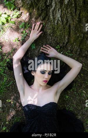 Pale woman in black dress lying on the ground in woods, dark mystery scene