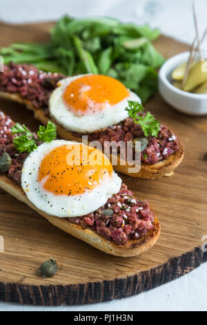 Beef tartare with pickled fried egg on top. - Stock Photo