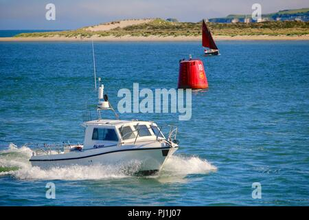 Poole, Dorset, England - June 02 2018: White motor boat speeds through the blue ocean past a marker buoy with a 10 knot speed limit - Stock Photo