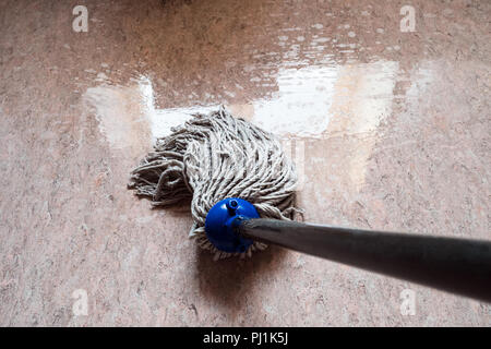 point-of-view shot of wiping floor by rope mop with reflection of the window in the wet floor - Stock Photo
