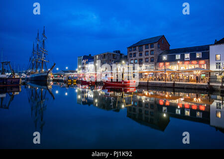 Beautiful reflections of the harbour side lights and restaurants on Plymouths Barbican area near the harbour - Stock Photo