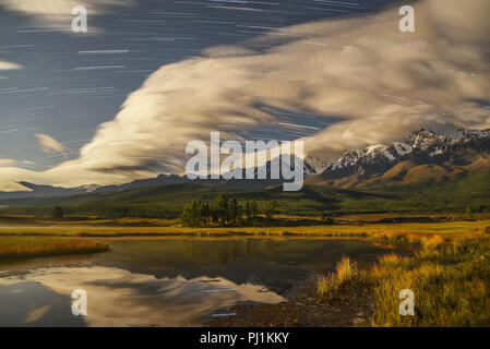 Amazing night landscape with snowy mountains, forest, trees, beautiful clouds on the sky and stars in the form of tracks, reflected in the smooth wate - Stock Photo